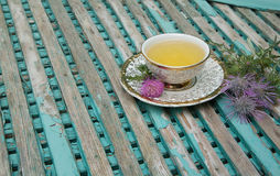 Milk thistle tea. A cup of milk thistle tea. Milk thistle blossoms are in the background stock photography