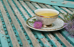 Milk thistle tea. A cup of milk thistle tea. Milk thistle blossoms are in the background royalty free stock photography