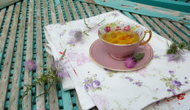 Milk thistle tea. A cup of milk thistle tea on a table cloth. Milk thistle blossoms are in the background royalty free stock photos