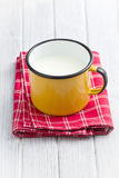 Milk in tin mug. On wooden table Royalty Free Stock Photography