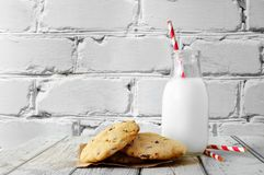 Milk in traditional bottle with chocolate chip cookies Royalty Free Stock Photography