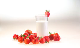 Milk in a transparent glass and berries of a ripe red strawberry. On a white background royalty free stock photography