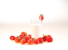 Milk in a transparent glass and berries of a ripe red strawberry. On a white background royalty free stock images