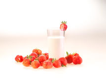 Milk in a transparent glass and berries of a ripe red strawberry. On a white background stock photography