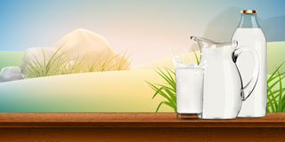 Milk in transparent glass, jug and bottle standing behind, with splash and lot of drops on shiny background Stock Photos