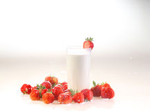 Milk in a transparent glass and a strawberry on a white backgrou. Nd, Fresh strawberry and milk royalty free stock image