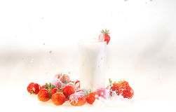 Milk in a transparent glass and a strawberry on a white backgrou. Milk splash in a glass, milk and a strawberry on a white background stock image