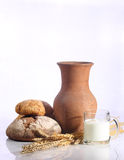 Milk in a transparent mug and fresh bread on a white background. Bread and milk stock photos