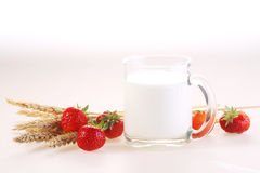 Milk in a transparent mug and a fresh strawberry on a white back. Ground stock photography