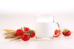 Milk in a transparent mug and a fresh strawberry. On a white background royalty free stock photo
