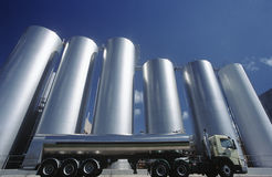 Milk transport truck parked alongside storage tanks Stock Photo