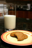 Milk vase and bitten cookie Royalty Free Stock Photography
