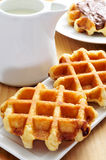 Milk and waffles. A pot with milk and some waffles in a plate, on a wooden table stock photography