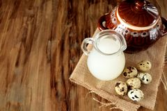 Milk whey in a glass jug. Milk whey, quail eggs and a clay pot on a wooden background. Farm products Royalty Free Stock Photo