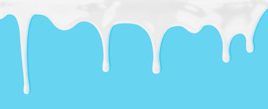 Milk or white liquid dripping on blue background Royalty Free Stock Photography