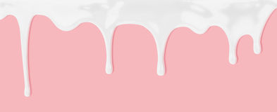Milk or white liquid dripping on pink background Royalty Free Stock Image