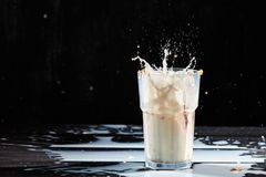 Milk or white liquid splash and oat flakes, muesli in the glass on a black background stock photos