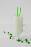 Milk yogurt smoothie cocktail green and white candy drop. Cocktail shake smoothie milkshake and green and white candy beads dragees Royalty Free Stock Images