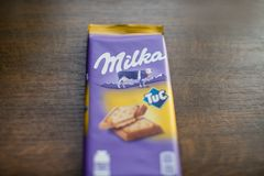 Milka chocolate bar with Tuc cracker with wooden background. Milka is a brand of chocolate confection by Mondelēz International royalty free stock photo
