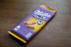 """Milka chokladstång med den Tuc smällaren med träbakgrund Milka är ett märke av chokladconfectionen vid internationella MondelÄ """"z arkivfoto"""