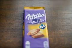 """Milka czekoladowy bar z Tuc krakersem z drewnianym tłem Milka jest gatunkiem czekoladowa słodycze MondelÄ """"z zawody międzynarodow zdjęcie royalty free"""