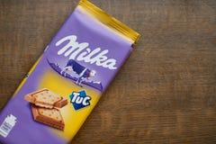 """Milkachocoladereep met Tuc-cracker met houten achtergrond Milka is een merk van chocoladegebak door Internationale MondelÄ """"z stock afbeeldingen"""