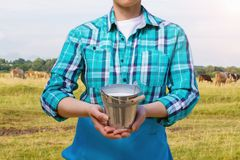 Milkmaid with a pail of milk . Milkmaid with a pail of milk on the background of the pasture Stock Photos
