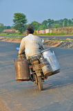 Milkman carrying milk on motor bike Royalty Free Stock Images