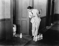 Milkman greeting baby at door Royalty Free Stock Images
