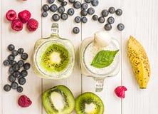 Milks shake da banana e do quivi em uns frascos de pedreiro com nata e decorações na parte superior e decoradas com mirtilos, ban Foto de Stock Royalty Free