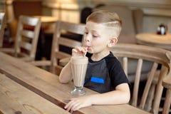 Milkshake мальчика выпивая сидя на таблице в кафе Стоковое Изображение RF