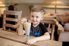 Milkshake мальчика выпивая сидя на таблице в кафе Стоковые Фотографии RF