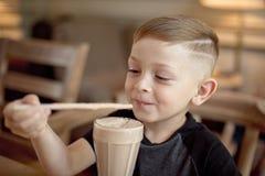 Milkshake мальчика выпивая сидя на таблице в кафе Стоковая Фотография