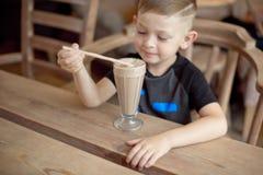 Milkshake мальчика выпивая сидя на таблице в кафе Стоковое Изображение