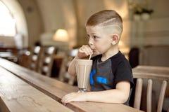 Milkshake мальчика выпивая сидя на таблице в кафе Стоковое фото RF