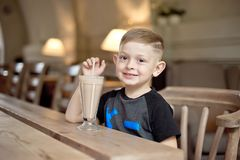 Milkshake мальчика выпивая сидя на таблице в кафе Стоковое Фото