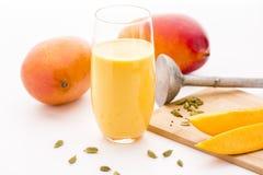 Milkshake манго, 2 манго и куски плодоовощ Стоковое фото RF