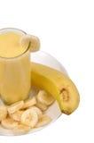Milkshake. Banana milkshake around banana slices on plate Stock Photography