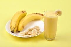 Milkshake. Banana milkshake around banana slices on plate Royalty Free Stock Images