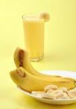 Milkshake. Bananas and slices on plate against milkshake Royalty Free Stock Images
