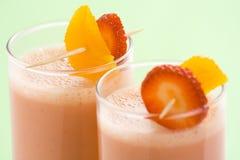 Milkshake alaranjado da banana da morango deliciosa Imagens de Stock Royalty Free