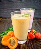 Milkshake apricot and strawberry in glassfulls on board Royalty Free Stock Photography