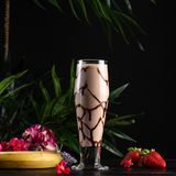 Milkshake with banana and chocolate in a tall glass on a dark background stock images