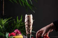 Milkshake with banana and chocolate in a tall glass on a dark background stock photo
