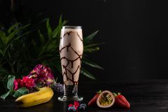 Milkshake with banana and chocolate in a tall glass on a dark background royalty free stock photography