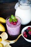 Milkshake with berries. Milkshake with raspberries, blueberries and banana in a glass jar at dark wooden table Royalty Free Stock Image