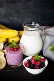 Milkshake with berries. Milkshake with raspberries, blueberries and banana in a glass jar at dark wooden table Royalty Free Stock Photos