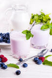 Milkshake with blueberries. Raspberries and mint Royalty Free Stock Images