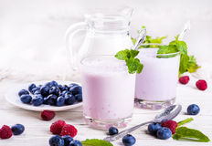 Milkshake with blueberries. Raspberries and mint Royalty Free Stock Photography