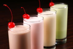 Milkshake cocktail. Diagonal row of four milkshake cocktails in the glasses garnished with cherries on the wooden table royalty free stock image